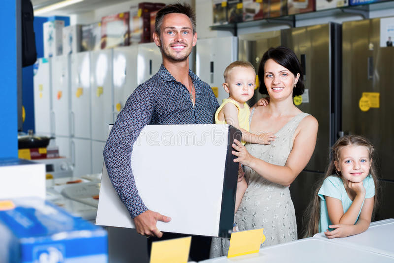 Couple with two kids holding box with electronics. Smiling couple with two kids holding box with new electronics in home appliance store royalty free stock image