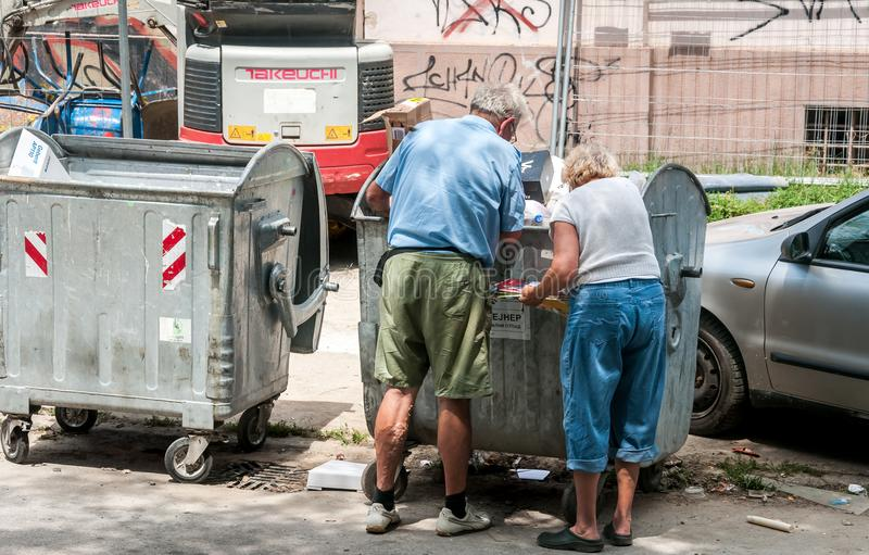 Couple of two older people looking and collecting things from old metal dumpster can, social issues concept. Novi Sad, Serbia. July - 15. 2018. Couple of two stock photography