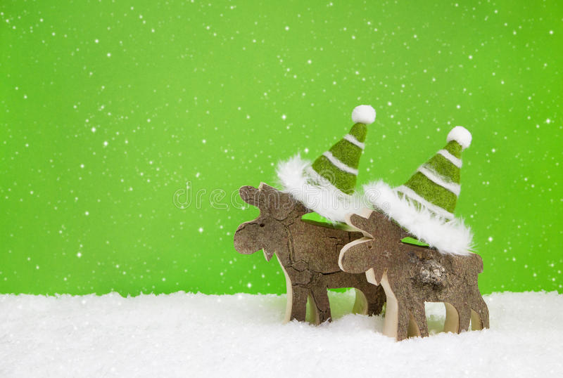 Couple of two wooden reindeer on green snowy christmas background. stock photo