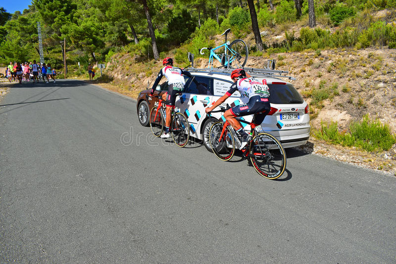 Cycle Racing Holding Onto Rival Team Car La Vuelta España. A couple of UAE Team Emirates riders hitch a ride with the AG2R team car. at the end of stage eight stock photos