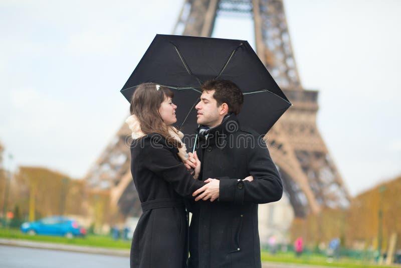 Couple with umbrella near Eiffel tower royalty free stock photo
