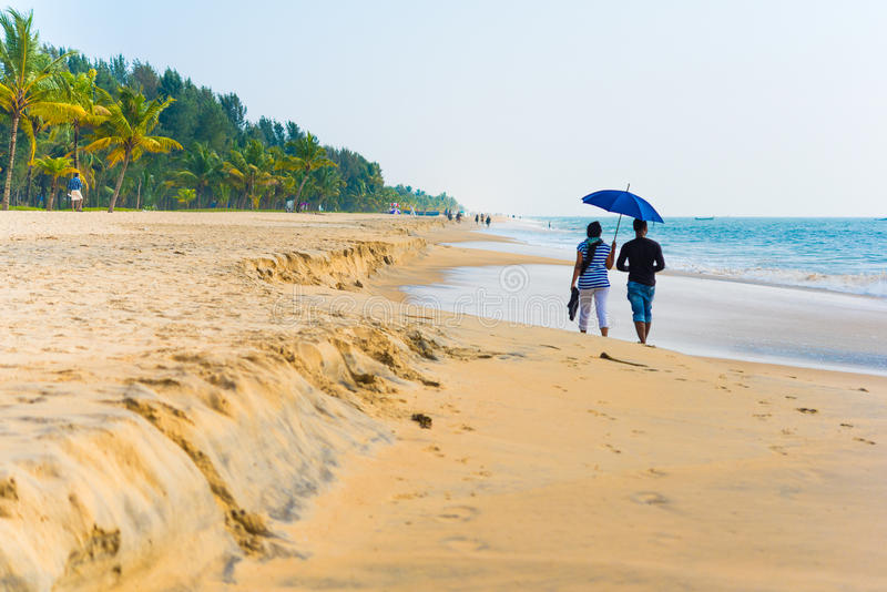Couple under umbrella walk on Marari Beach stock images
