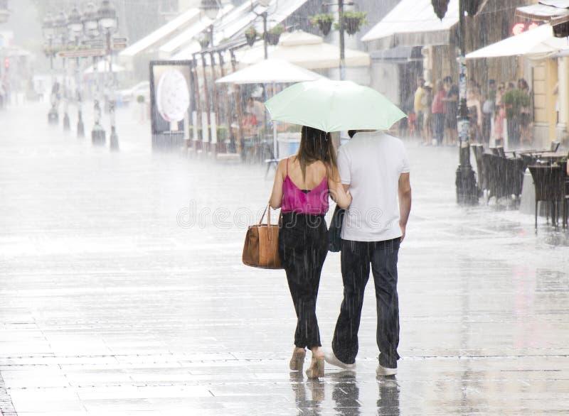 Couple under umbrella walking in heavy summer rain royalty free stock photos