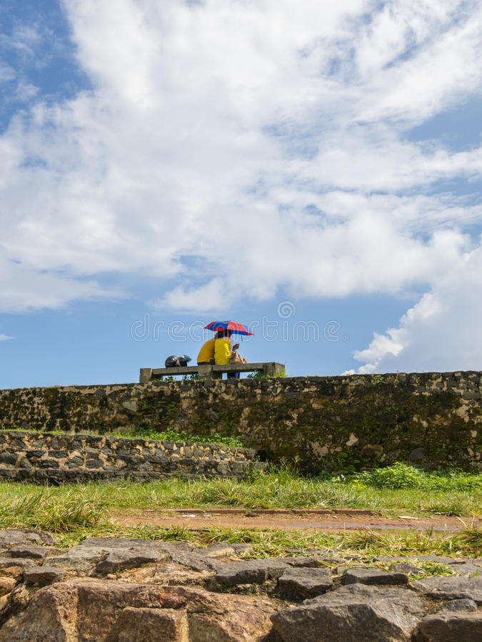 Couple under umbrella at the wall. In Galle Srilanka royalty free stock image