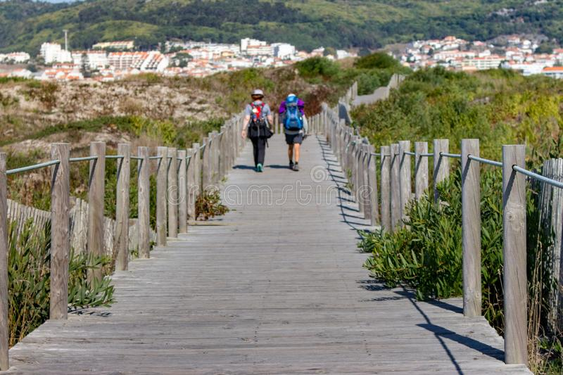 Couple of unknown pilgrims from the back walking on wooden path. Camino de Santiago way concept. Walking pilgrims with backpacks. Couple of unknown pilgrims stock image