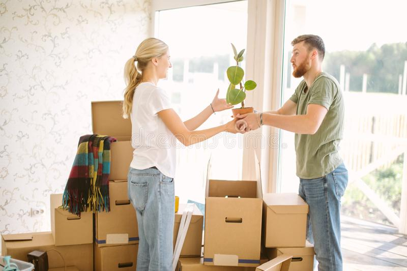 Couple unpack boxes in new home. Woman giving flower to her husband royalty free stock images
