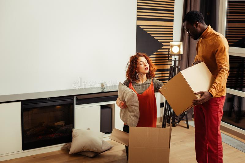 Couple unpacking boxes with pillows after moving to new house royalty free stock photography