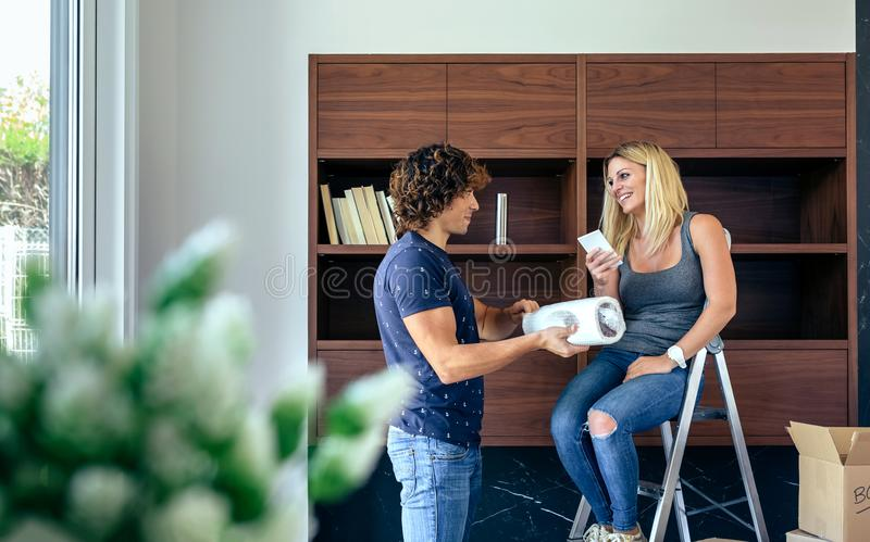 Couple unpacking boxes and placing books stock photography