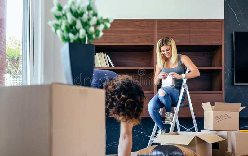 Couple unpacking boxes and placing books. Couple unpacking moving boxes and placing things on the shelf royalty free stock photography