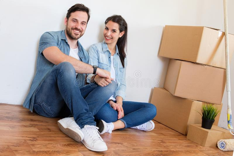 Portrait of cheerful young couple sitting in new house royalty free stock photo
