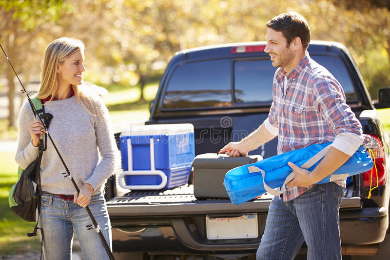 Couple Unpacking Pick Up Truck On Camping Holiday stock photography