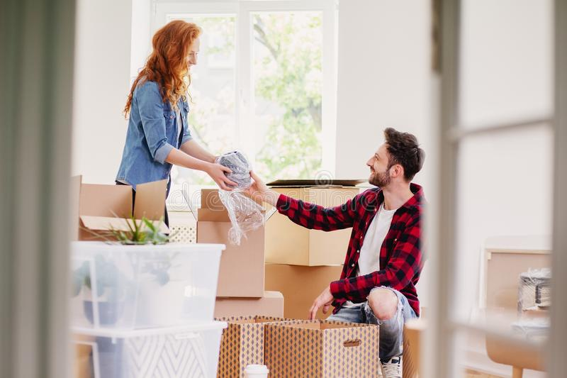 Couple unpacking stuff from carton boxes while furnishing interior. Concept stock photo