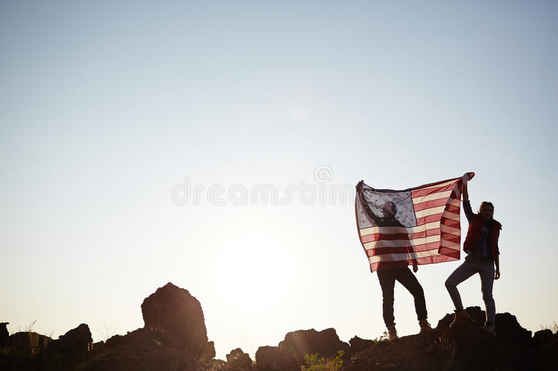 Couple with USA Flag on Mountain Top. Wide shot image with copy space of backlit couple standing on mountain top against the sun and sky holding big USA banner royalty free stock photography