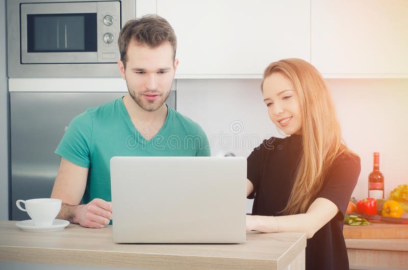 Couple uses the computer in the kitchen stock image
