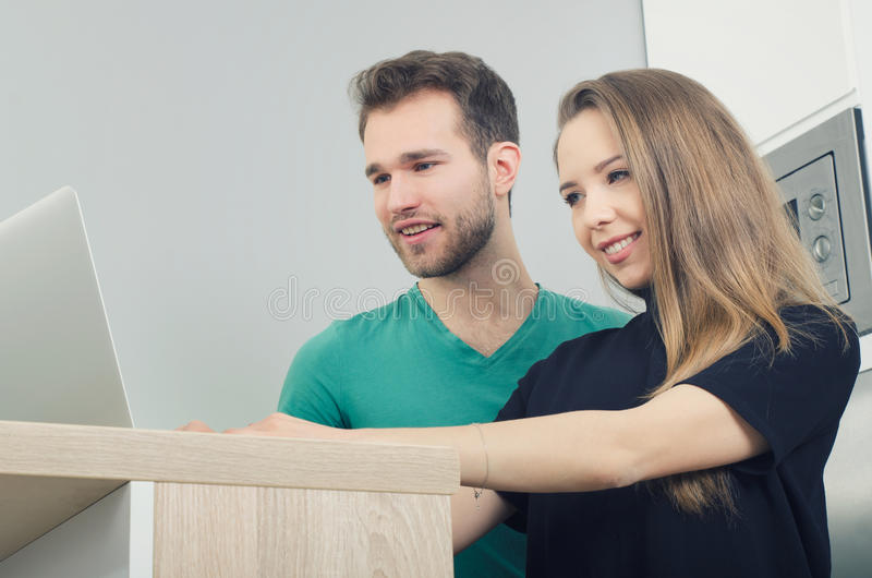 Couple uses the computer in the kitchen royalty free stock image