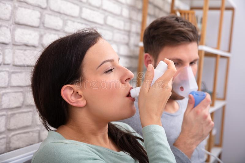 Couple Using Asthma Inhaler. Close-up Of Couple Suffering Asthma Using Inhaler At Home royalty free stock image