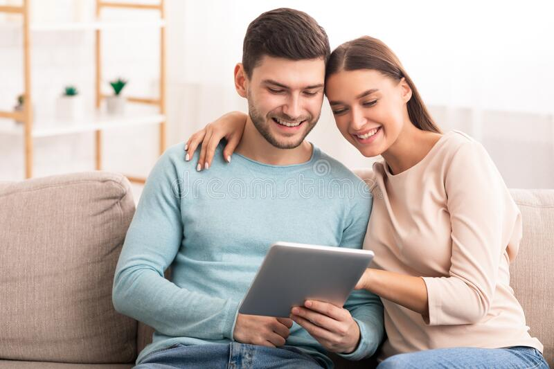 Couple Using Digital Tablet Hugging Watching Film At Home stock photos