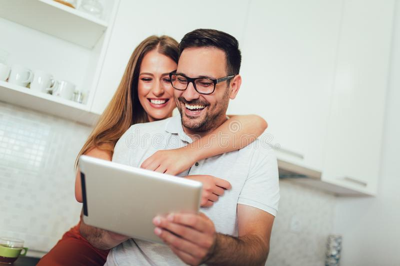 Couple using digital tablet in the kitchen royalty free stock images