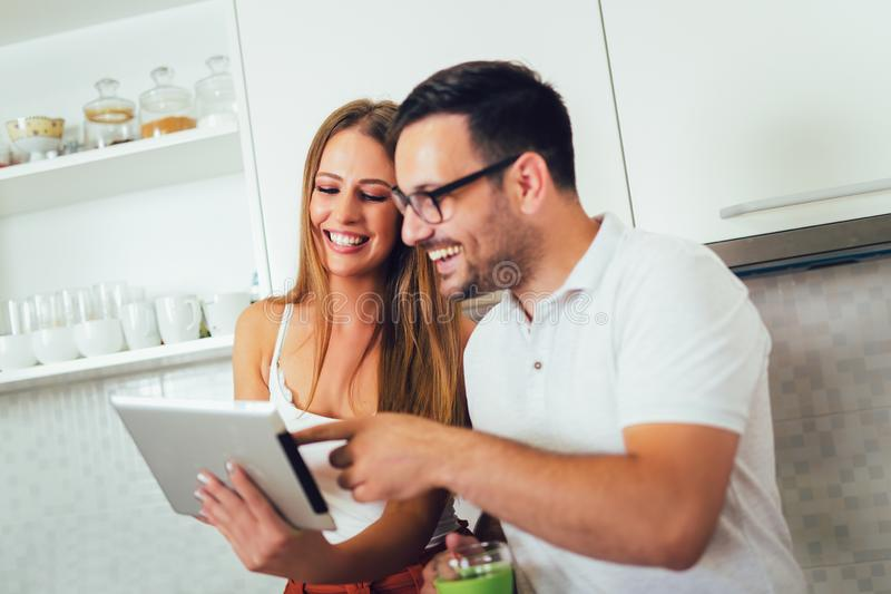 Couple using digital tablet in the kitchen royalty free stock photography