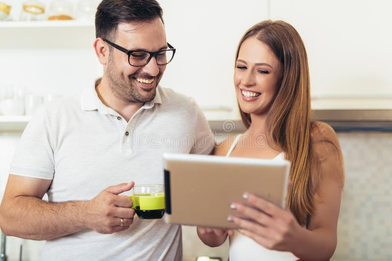 Couple using digital tablet in the kitchen stock image