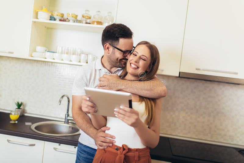 Couple using digital tablet in the kitchen stock images