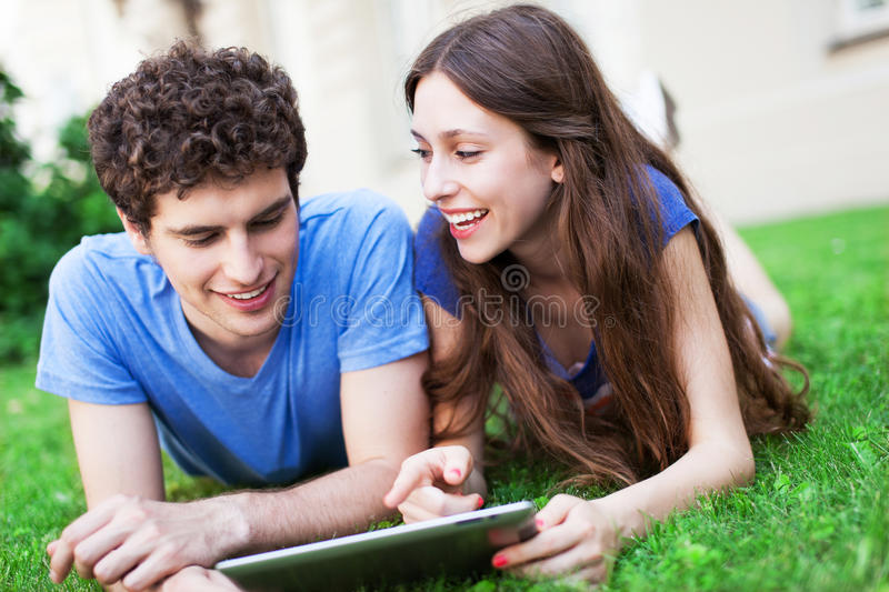 Download Couple Using Digital Tablet On Lawn Stock Photo - Image: 32387010