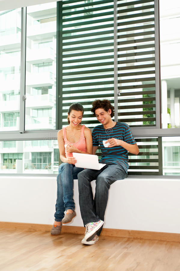 Couple Using Laptop. A young and attractive couple using laptop by the windows in their new home royalty free stock image