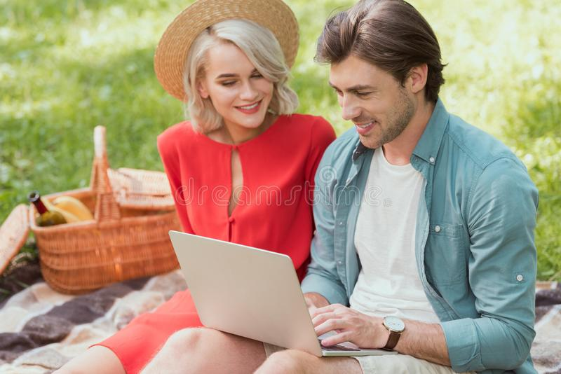 couple using laptop on blanket royalty free stock images