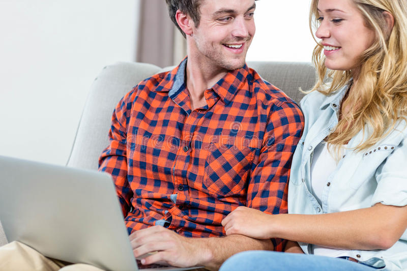 Couple using laptop on the couch. In the living room royalty free stock image