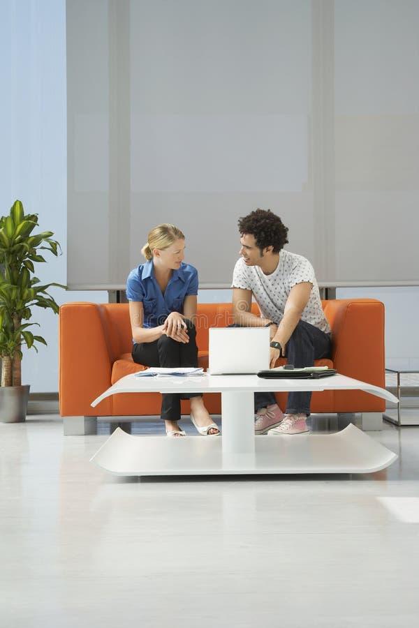 Couple Using Laptop On Orange Sofa At Office stock photos