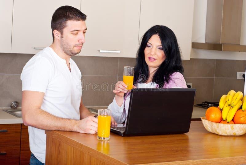 Couple using laptop in their kitchen royalty free stock photos