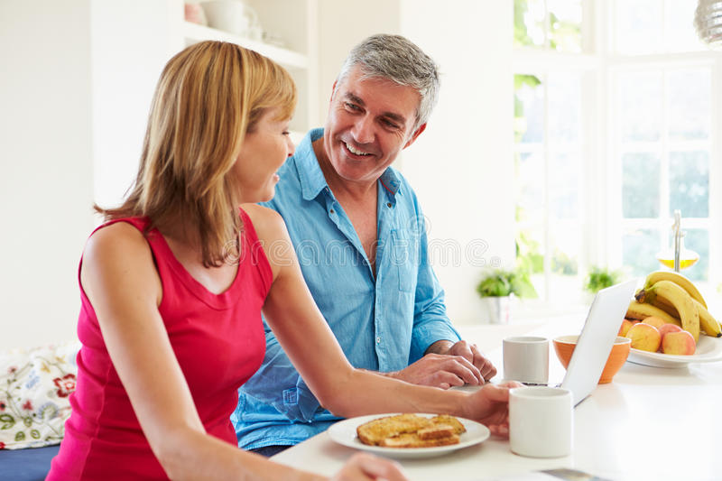 Couple Using Laptop Whilst Having Breakfast In Kitchen. Smiling At Each Other stock photos