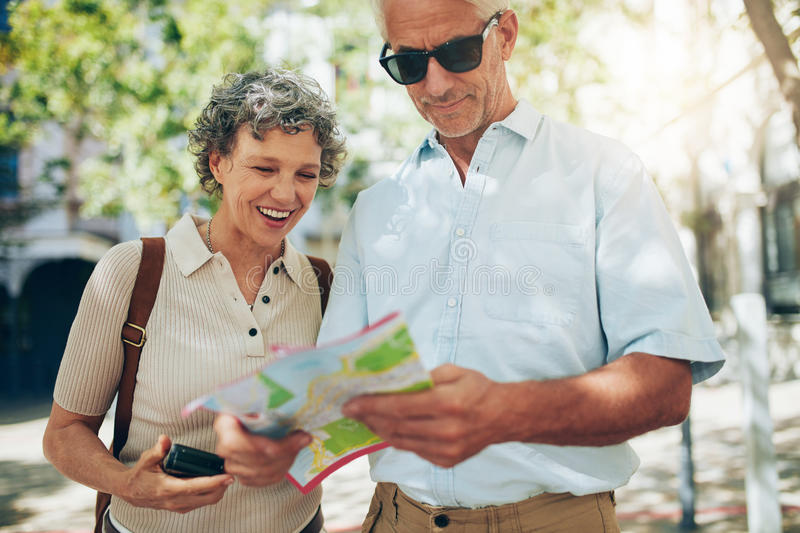 Couple using a map on vacation stock photo
