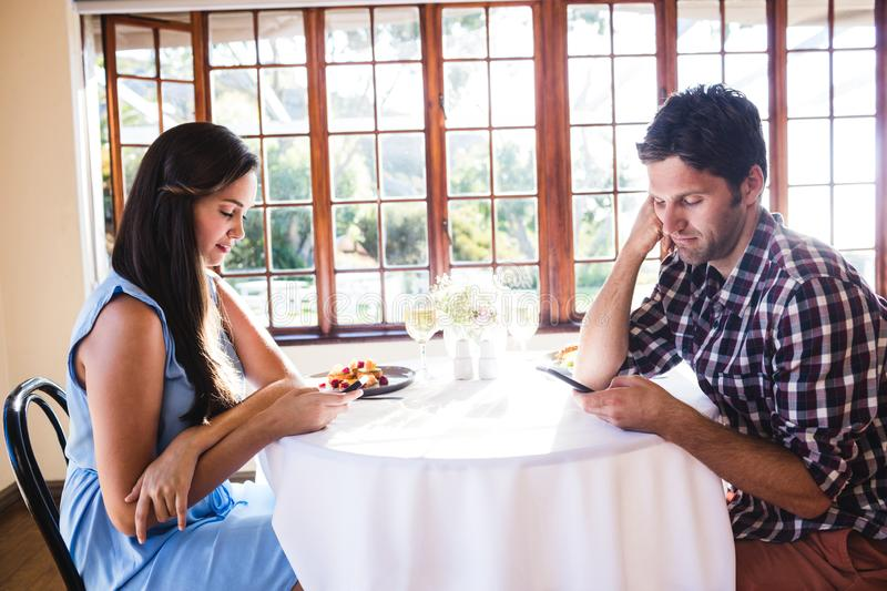 Couple using mobile phone in restaurant stock photos