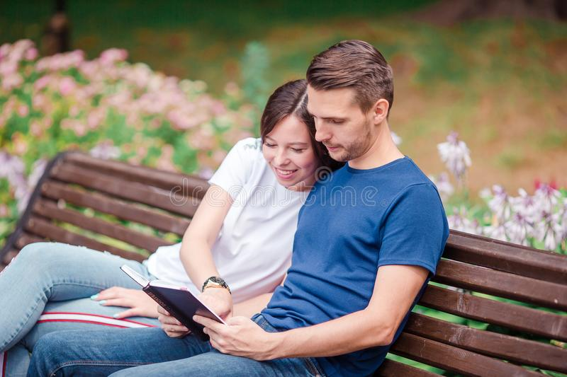 Couple using tablet and cellphone in public park. stock image