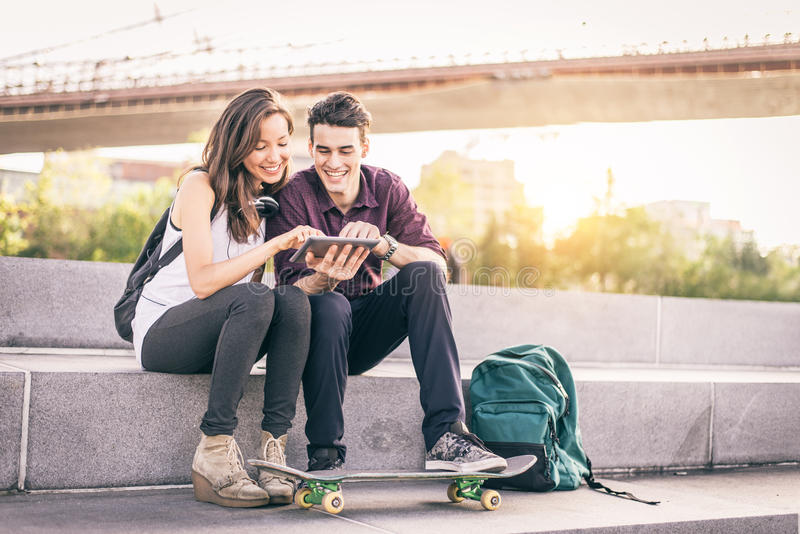 Couple using tablet outdoors stock images