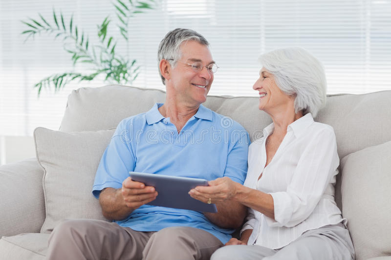 Download Couple Using A Tablet Pc Sitting On The Couch Stock Photo - Image: 33052172