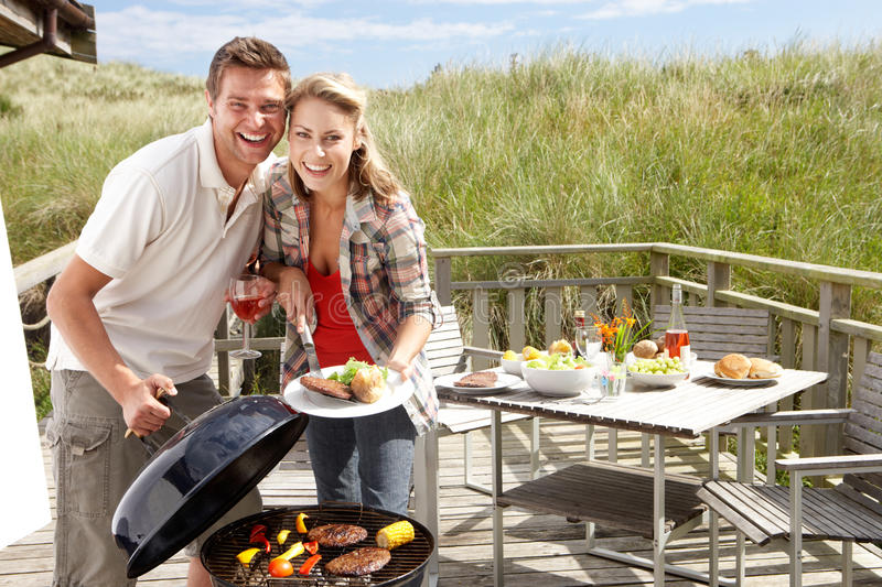 Couple on vacation having barbecue. Smiling at camera stock image