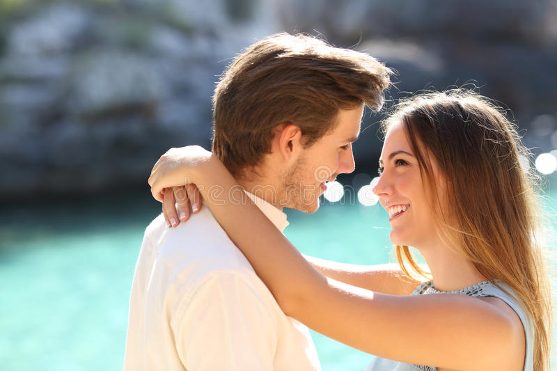 Couple in vacations looking each other ready to kiss royalty free stock photo