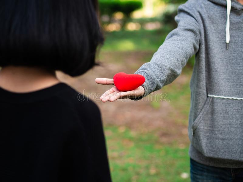 Couple on Valentines day. The man gives red heart to the woman in the park. Love, Valentines Day stock image