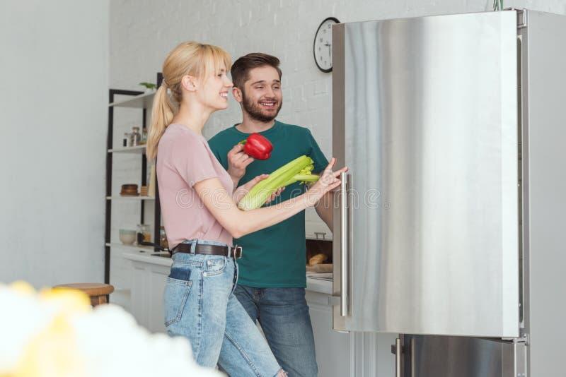 Couple of vegans taking vegetables from fridge. In kitchen stock images