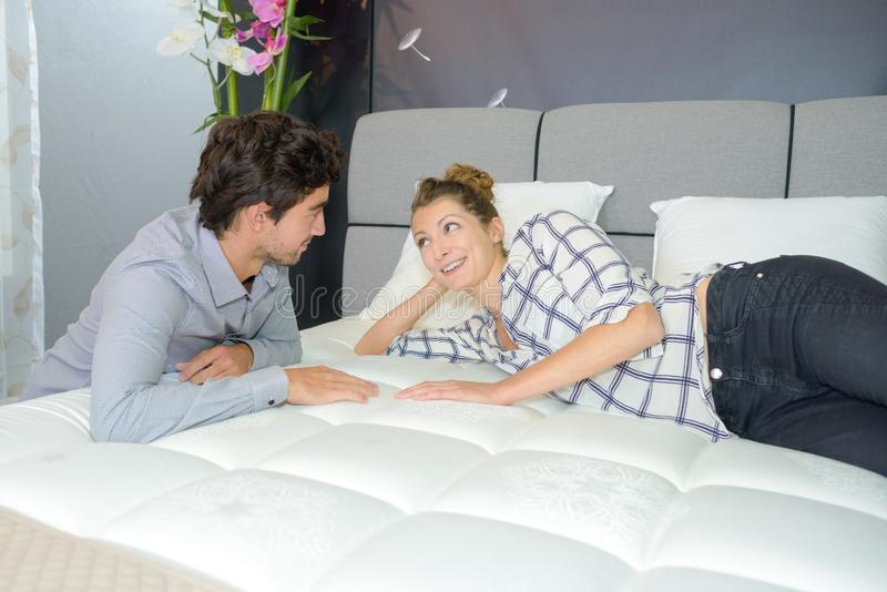 Couple viewing new mattress royalty free stock image