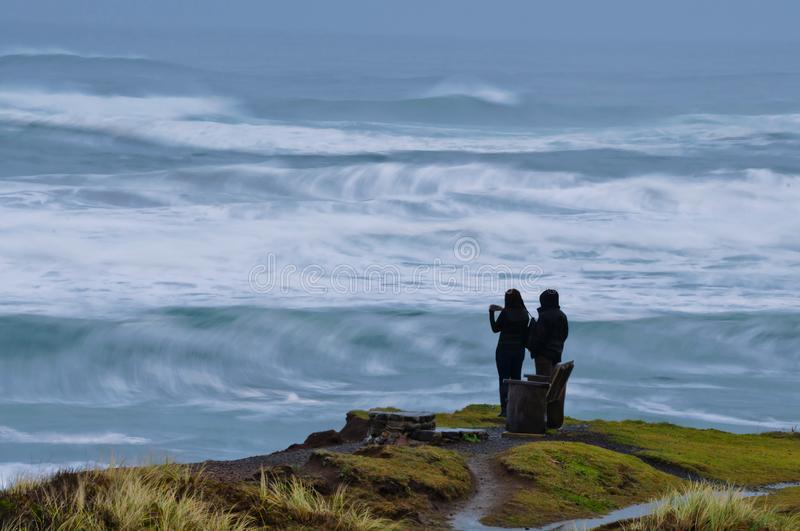 Couple viewing the Pacific Ocean at dusk in Oregon, State. Man and woman standing on a cliff viewing the Pacific Ocean stock photos