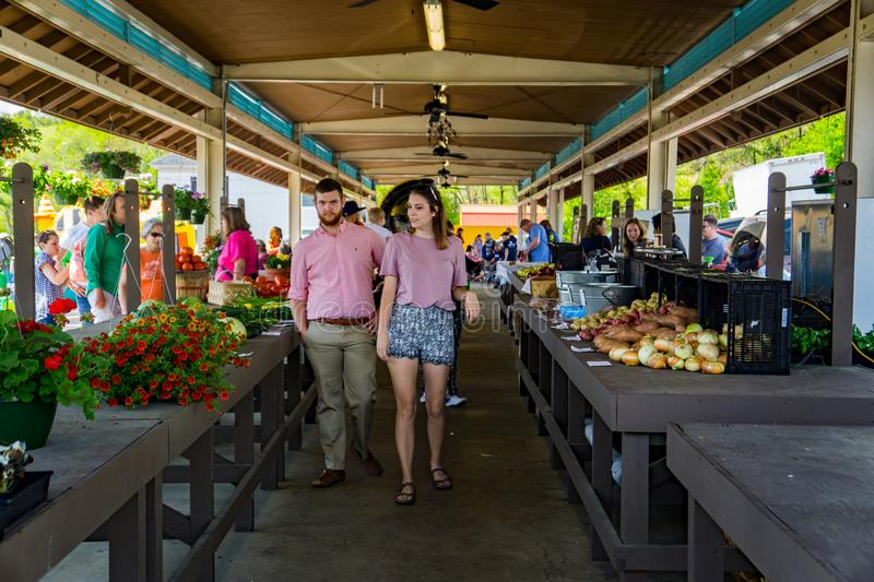 Couple at the Vinton Farmers Market. Vinton, VA – April 28th: Couple shopping at the Vinton Farmers Market during the Annual Dogwood Festival located in stock image