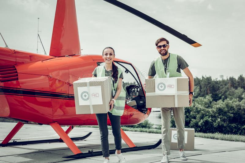 Couple of volunteers holding parcels with humanitarian help. With humanitarian help. Couple of volunteers holding parcels with humanitarian help standing near royalty free stock photos