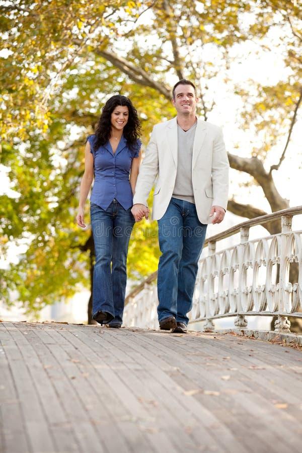 Couple Walk Bridge. A couple walking on a bridge in a park royalty free stock photography