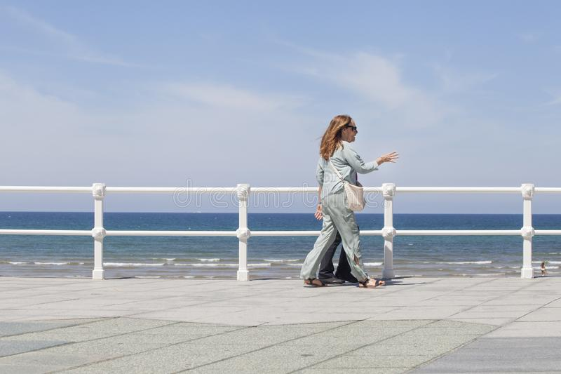 Couple walk on seafront of Gijón stock image