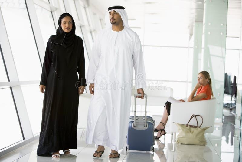 Couple walking through airport departure lounge stock photo
