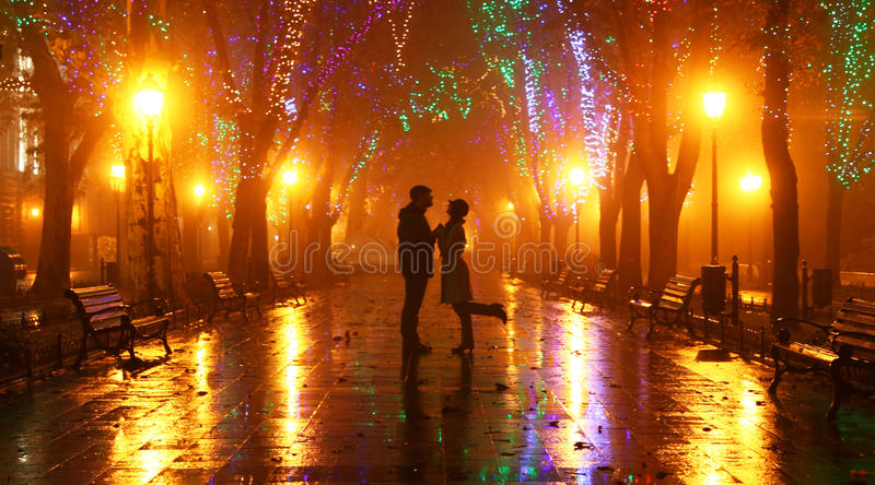 Couple walking at alley in night lights royalty free stock photography