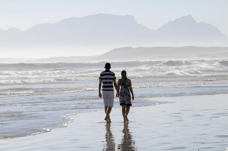 Couple walking along beach in South Africa. Couple walking hand in hand on the wet sandy beach at Strand in the Western Cape South Africa. In the distance is the royalty free stock images